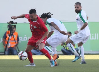 Mazin Fyad, center, of Iraq in action against Abdullah Jaber, left, of Palestine during a friendly match between Palestine and Iraq at the Faisal Al-Husseini International Stadium in the town of Al-Ram northeast of Jerusalem, on August 4, 2018.