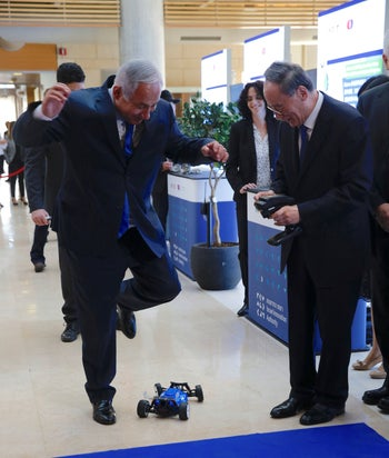 Prime Minister Benjamin Netanyahu avoids a toy car controlled by China's Vice President Wang Qishan as they tour the Israeli Innovation Summit in Jerusalem, Wednesday, Oct. 24, 2018