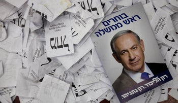 File photo: Election campaign poster with the image of Israeli Prime Minister Benjamin Netanyahu lies among ballot papers at his party's election headquarters in Tel Aviv, March 18, 2015.