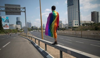 LGBT community members block a highway during a protest against a surrogate bill in Tel Aviv, Israel, Sunday, July 22, 2018.