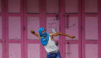 File Photo: Palestinian protester throws a stone during clashes with Israeli soldiers, Hebron, West Bank.