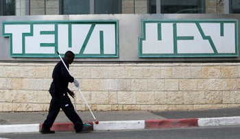 FILE PHOTO: A man cleans near the logo of Teva Pharmaceutical Industries at their plant in Jerusalem December 14, 2017.