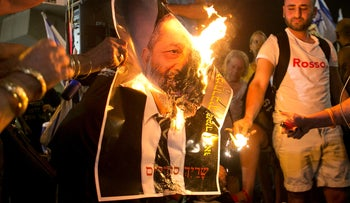 FILE: Protesters burn a photo of Shas chairman Arye Deri in southern Tel Aviv