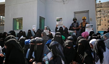 """Yemeni police troopers, background, stand guard at a door of the U.N. offices as women take part in a protest calling for the reopening of Sanaa airport to receive medical aid, in front of the U.N. offices in Sanaa, Yemen, Monday, Dec. 10, 2018. Arabic writing on banners from left that reads """"Open Sanaa airport to limit the suffering and deaths!"""" and """"Medicine is life, open Sanaa airport to receive medical aids."""""""