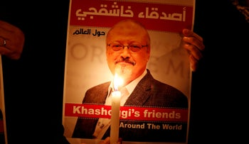FILE PHOTO: A demonstrator holds a poster with a picture of journalist Jamal Khashoggi outside the Saudi Arabia consulate in Istanbul, October 24, 2018.