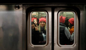 """A group of people wearing """"pussyhats"""" ride the subway at 42nd Street as they head toward the Women'sMarch in Manhattan, New York City. January 20, 2018"""
