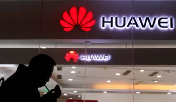 FILE: In this Dec. 6, 2018, file photo, a man lights a cigarette outside a Huawei retail shop in Beijing.