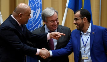 Head of Houthi delegation Mohammed Abdul-Salam (R) and Yemeni Foreign Minister Khaled al-Yaman (L) shake hands, during the Yemen peace talks, Sweden, December 13, 2018.