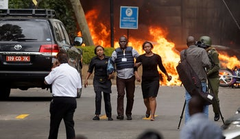 Security forces help civilians flee the scene as cars burn at a hotel complex in Nairobi, Kenya on , Jan. 15, 2019.