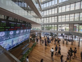 Visitors stand in front of a stock market ticker screen in the lobby of the Tel Aviv Stock Exchange (TASE) in Tel Aviv, Israel, on Thursday, Aug. 4, 2016.