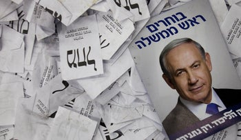 An election campaign poster with the image of Israeli Prime Minister Benjamin Netanyahu lies among ballot papers at his party's election headquarters in Tel Aviv. March 18, 2015