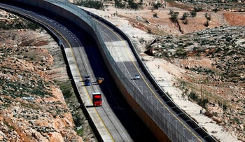 Cars drive on the new Israeli road divided by a wall to separate Palestinians and Israelis in East Jerusalem, January 10, 2019.