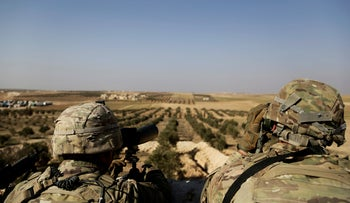 American troops look out toward the border with Turkey from a small outpost near the town of Manbij, northern Syria, February 7, 2018.