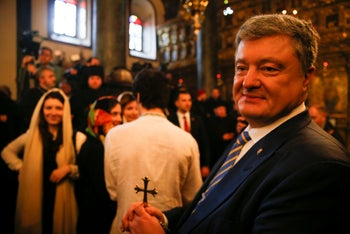 Ukrainian President Petro Poroshenko, right, holding a cross during a symbolic ceremony sanctifying the Ukrainian church's independence from the Russian Orthodox Church, Istanbul, January 6, 2019.
