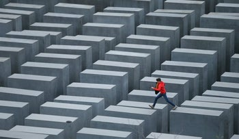 A boy hops from one to another of the 2711 stellae at the Memorial to the Murdered Jews of Europe in Berlin, Germany. October 28, 2013