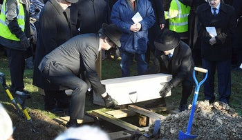 A coffin with the remains of six unidentified Holocaust victims is buried at the United Synagogue's New Cemetery in Bushey, England, Sunday Jan. 20, 2019