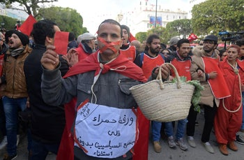 A Tunisian man wears a banner and holds a basket to complain about the high cost of living, during a rally marking the eighth anniversary of the 2011 revolution in front of the headquarter of the Tunisian General Labour Union in the capital Tunis on January 14, 2019.