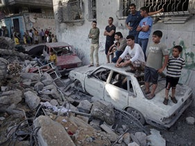 Palestinians look the damage of a destroyed house where five members of the Ghannam family were killed in an Israeli missile strike early morning in Rafah refugee camp, southern Gaza Strip, Friday, July 11, 2014.