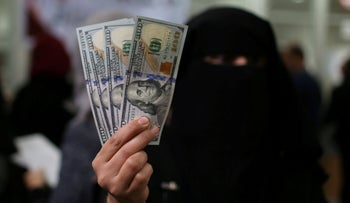A Palestinian Hamas-hired civil servant displays U.S. Dollar banknotes after receiving her salary paid by Qatar, in Khan Younis in the southern Gaza Strip December 7, 2018.