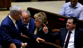 Israeli Prime Minister Benjamin Netanyahu chats with Ayman Odeh, head of the Joint Arab List, in the plenum at the knesset, Israel's parliament, in Jerusalem December 26, 2018.