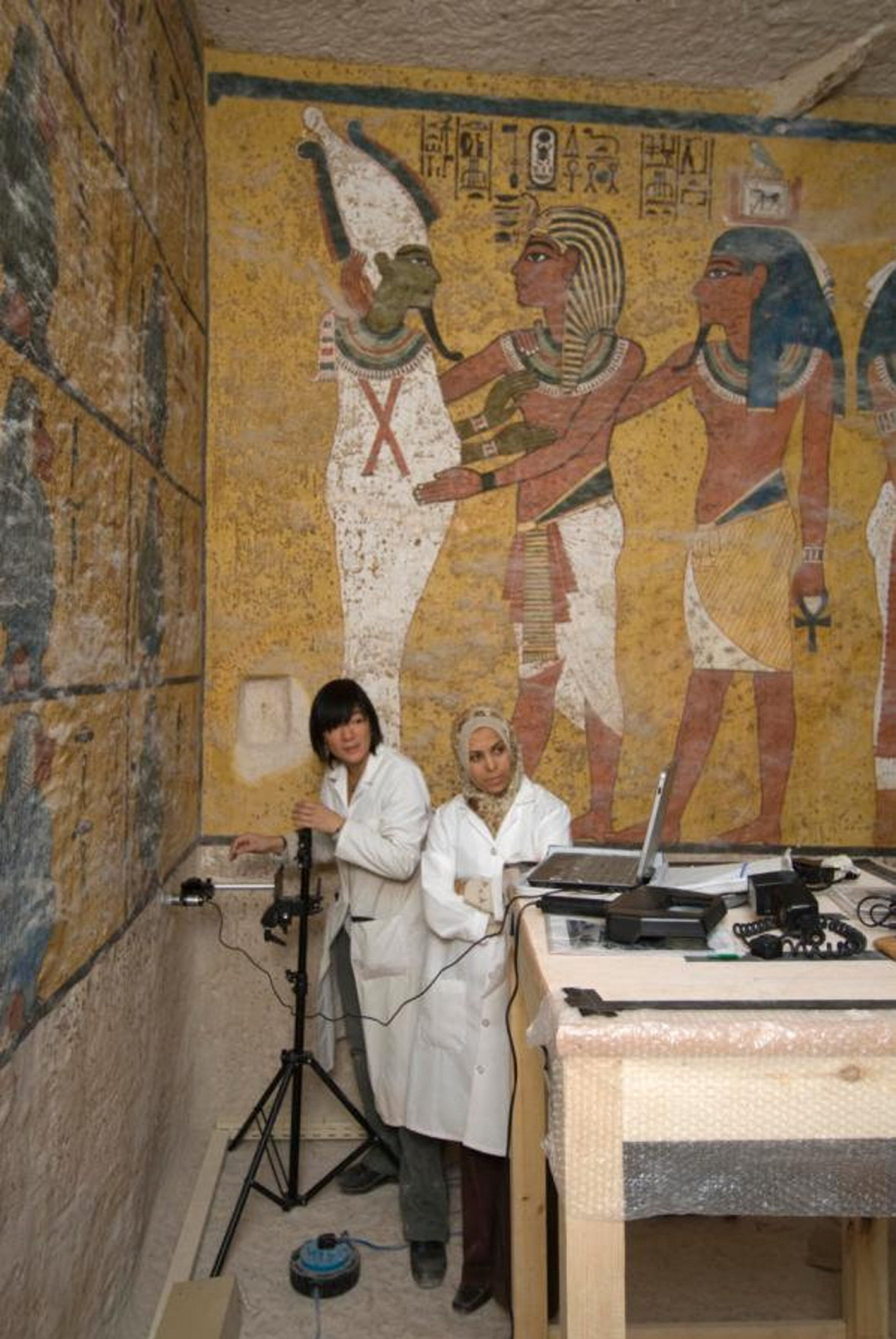 Conservators using a portable microscope linked to a tablet to monitor the paintings on the west wall of Tutankhamun's Tomb, Egypt, February 2009.