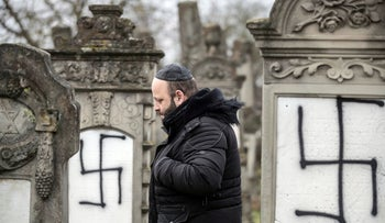 File photo: A member of the Jewish community walks among defaced gravestones at the Jewish cemetery of Herrlisheim, near Strasbourg, France, December 14, 2018.