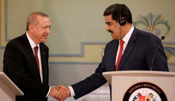 Turkish President Tayyip Erdogan and Venezuela's President Nicolas Maduro shake hands during a news conference after an agreement-signing ceremony between Turkey and Venezuela at Miraflores Palace in Caracas, Venezuela December 3, 2018.
