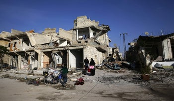 Picture shows half-ruined buildings along a street in Aleppo, Syria, against the backdrop of a bright deep blue sky.