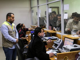 Postal wokers aid Palestinians arriving at the central post office in Gaza City to receive financial aid from the Qatari government given to impoverished Palestinian families, January 26, 2019.