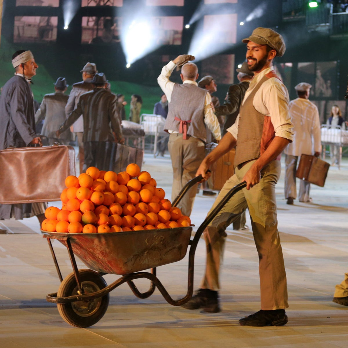 Actors playing Jewish members of the HeHalutz movement carrying oranges, as part of the national ceremony for the 70th anniversary of Israel.