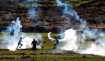 Palestinians protesting against land seizures for Jewish settlements, run to avoid tear gas fired by Israeli troops in the village of Al-Mughayyir, north of Ramallah, January 25, 2019.