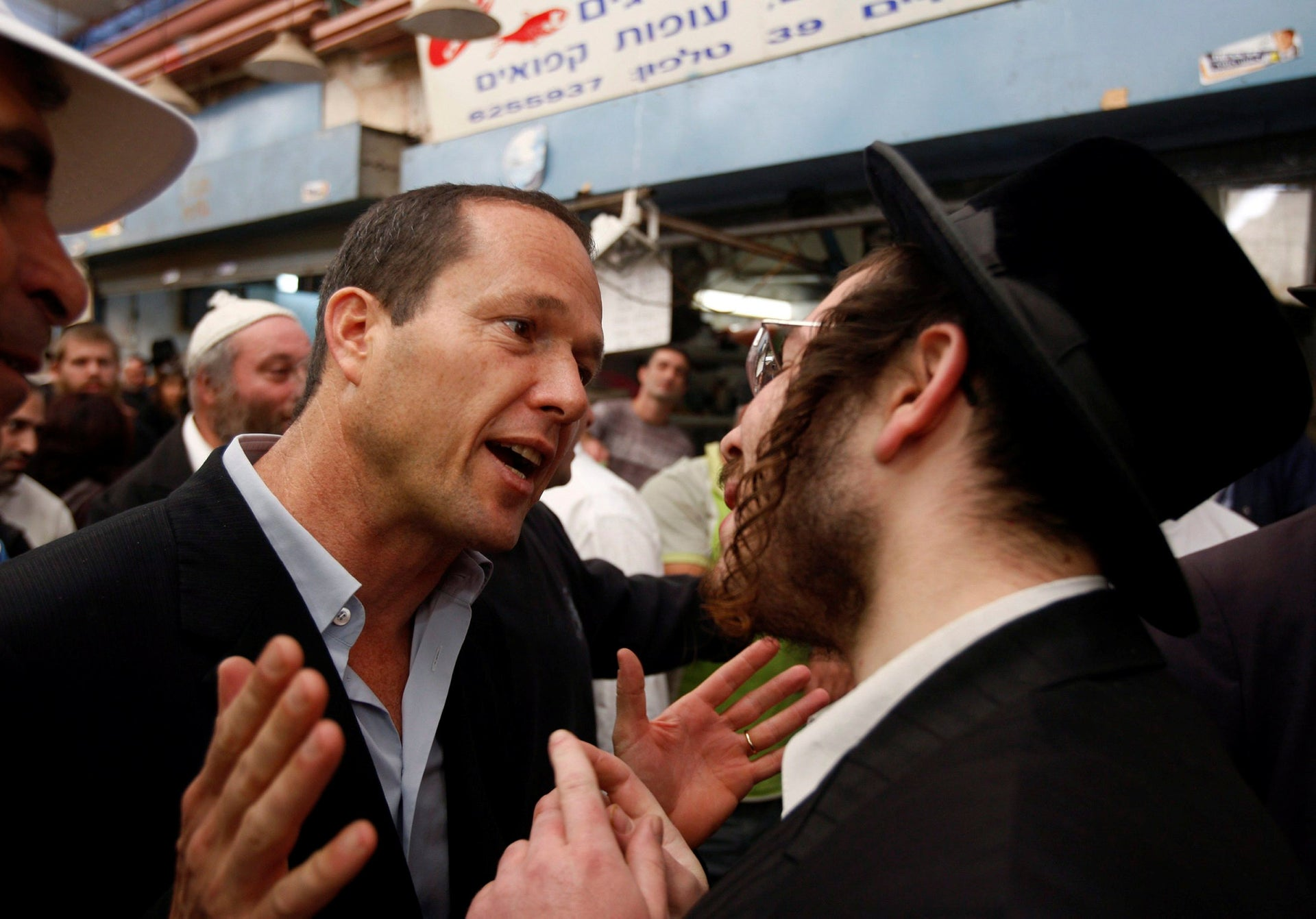 Nir Barkat (L), a Jerusalem mayoral candidate, speaks to an ultra-Orthodox Jew during a visit to a fruit and vegetable market in Jerusalem November 6, 2008. An Israeli mayoral election in Jerusalem has turned the holy city into a political battleground between secular and ultra-Orthodox Jews