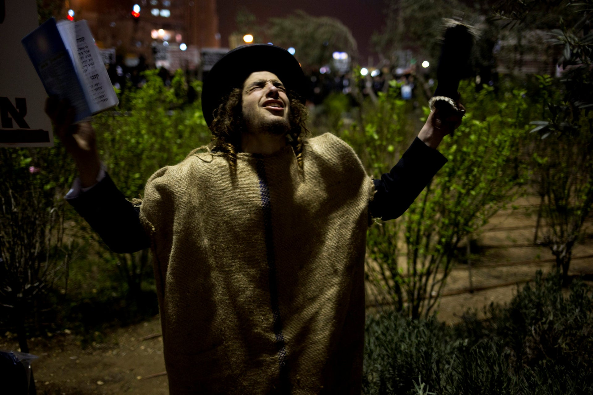 An ultra Orthodox Jew prays during a protest against the Israeli government's decision to draft the ultra Orthodox into military service, in Jerusalem on Wednesday, March 19, 2014.