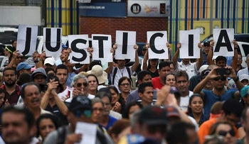 """Venezuelan opposition supporters holding up letters reading """"Justice"""" gather to listen to the head of Venezuela's National Assembly and the country's self-proclaimed """"acting president"""" Juan Guaido, during a rally in Caracas, on January 26, 2019"""