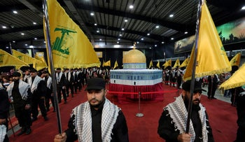 File photo: Hezbollah members carry Hezbollah flags as they stand in front of a replica of the Dome of the Rock during a rally on June 23, 2017.