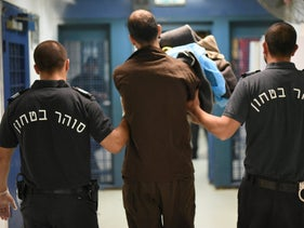 Israel Prison Service officials escorting a prisoner in the security wing of an Israeli jail, May 3, 2017