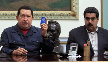 Venezuela's President Hugo Chavez, left, holds up a copy of the Venezuelan national constitution as his Vice President Nicolas Maduro looks on during a televised speech at Miraflores presidential palace in Caracas, Venezuela.