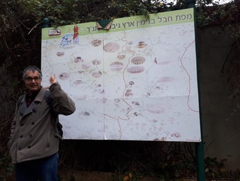 Emek Shaveh CEO Yonatan Mizrahi in front of a Hebrew-language tourist information map at Tel Shiloh, in the West Bank.