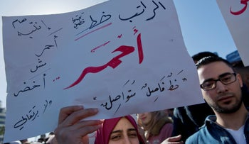"""A protester holds a placard that reads in Arabic, """"my salary is a red line,"""" during a general strike protesting the Palestinian Social Security Law, Ramallah, West Bank, January 15, 2019."""