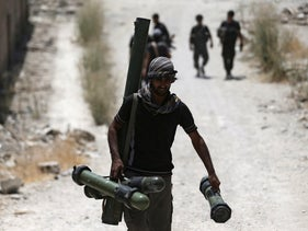 A fighter from the Free Syrian Army's Al Rahman legion carries a weapon as he walks towards his position on the front line against the forces of Syria's President Bashar al-Assad in Jobar, a suburb of Damascus, Syria.