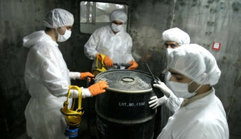 "FILE PHOTO: Iranian technicians lift a barrel of ""yellow cake"" to feed it into the processing line of Uranium Conversion Facility (UCF) in Isfahan, about 420 kM south of Tehran, on August 8, 2005."