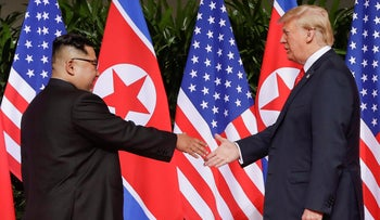 U.S. President Donald Trump reaches to shake hands with North Korea leader Kim Jong Un in Singapore. June 6, 2018.