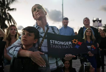 Taly Kogon and her son Leo, 10, listen to speakers during an interfaith vigil against anti-Semitism and hate at the Holocaust Memorial in Miami Beach, Fla. Oct. 30, 2018
