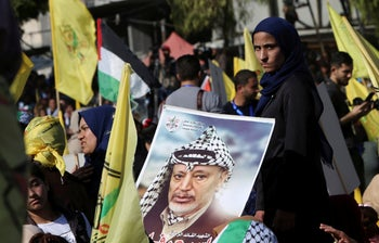Palestinians celebrating while waving a picture of late Palestinian leader Yasser Arafat during a rally to commemorate the 14th anniversary of his death of Arafat, Gaza City, November 20, 2018.