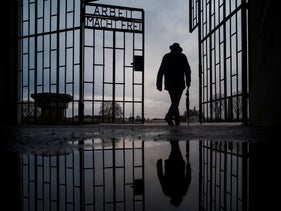 A man walks through the gate of the Sachsenhausen Nazi death camp on the International Holocaust Remembrance Day, in Oranienburg, Germany. Jan. 27, 2019