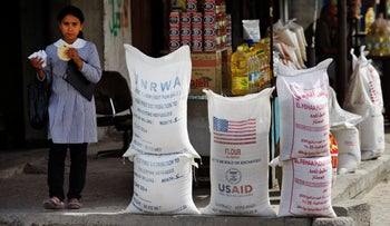 A Palestinian pupil walks past sacks of flour, some part of humanitarian aid by UNRWA and USAID, Shatie refugee camp, Gaza City, June 6, 2010.