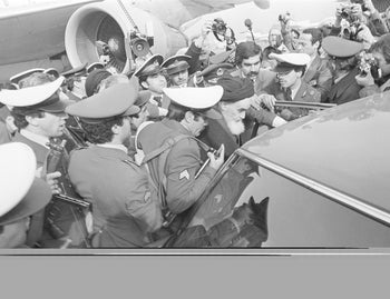 In this Feb. 1, 1979 file photo, exiled Ayatollah Ruhollah Khomeini has a heavy escort as he enters car to leave the airport in Tehran, Iran.