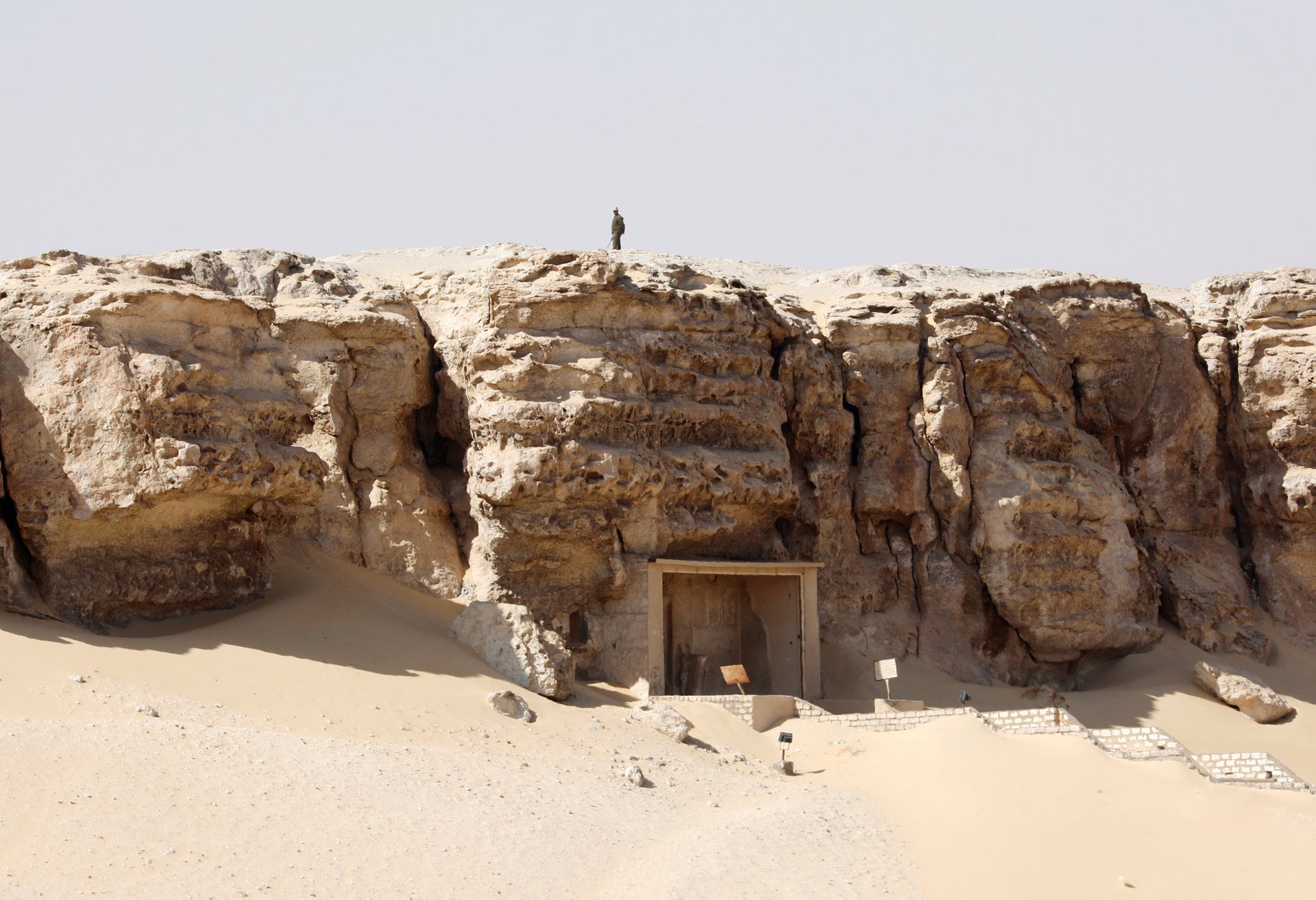 A member of security personnel stands atop of a cliff as he guards the presentation of a new discovery at Tuna el-Gebel archaeological site in Minya Governorate, Egypt, February 2, 2019.