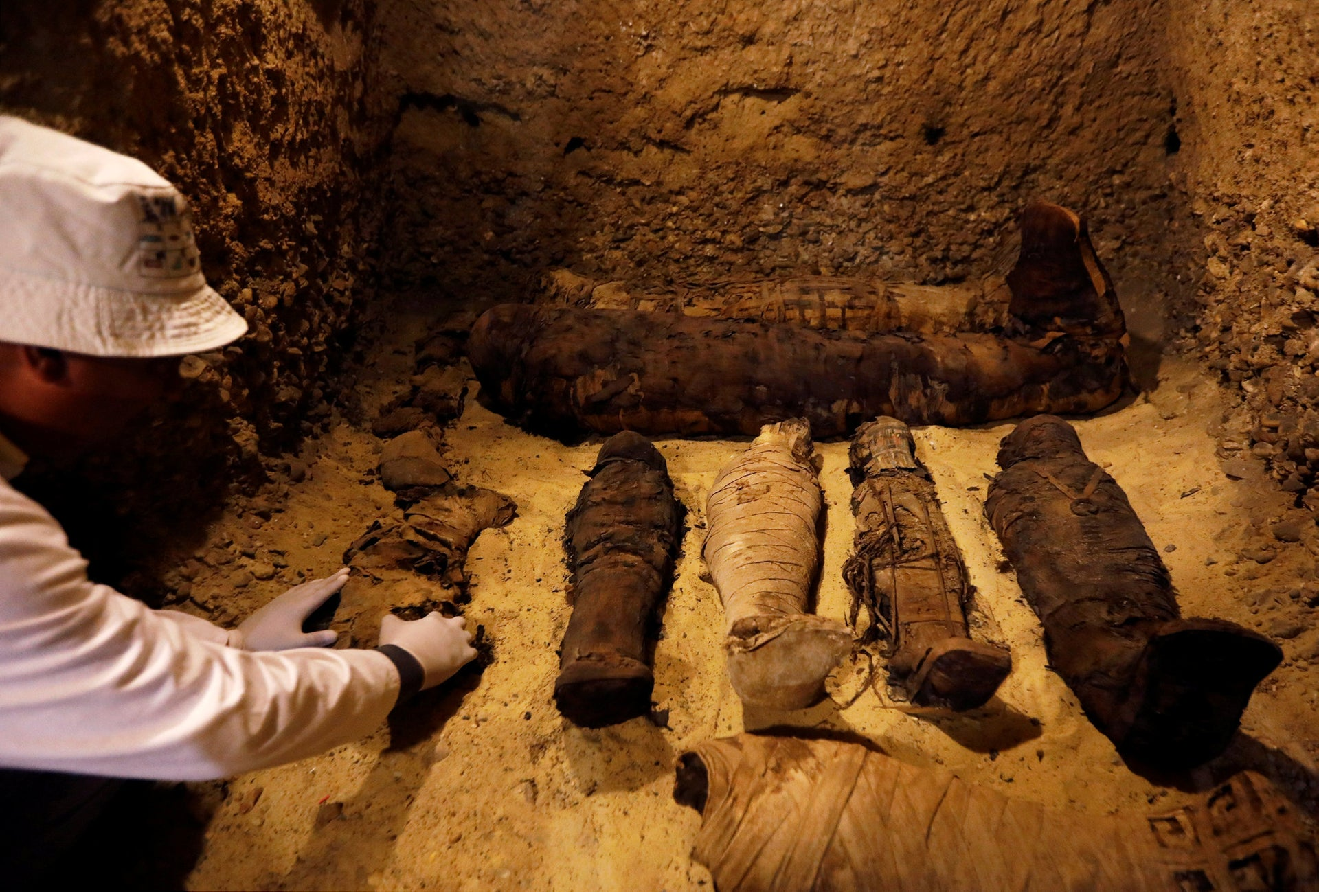 A Egyptian archaeologist examines mummies inside a tomb during the presentation of a new discovery at Tuna el-Gebel archaeological site in Minya Governorate, Egypt, February 2, 2019.