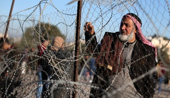 A Palestinian man stands by a fence as he waits for a travel permit to leave Gaza through Rafah border crossing with Egypt, February 3, 2019.